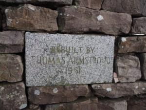 Plaque showing the cairn was rebuilt by Thomas Armstrong in 1961