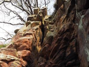The red sandstone rock towers above the narrow riverbank