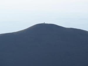 A zoom shot of two walkers on the summit of Dufton Pike