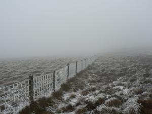 Following a frozen fence on to Grey Nag