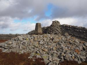 The trig point and cairn on the summit of Grey Nag
