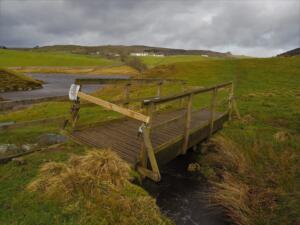 A broken footbridge on the path along the reservoir shore