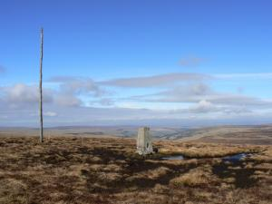 The trig point and wooden pole on the top of Killhope Law